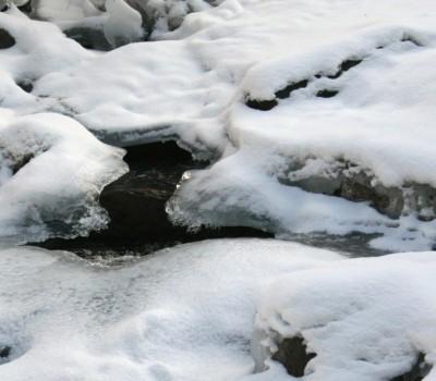Gebirgsbach unter dem Eis